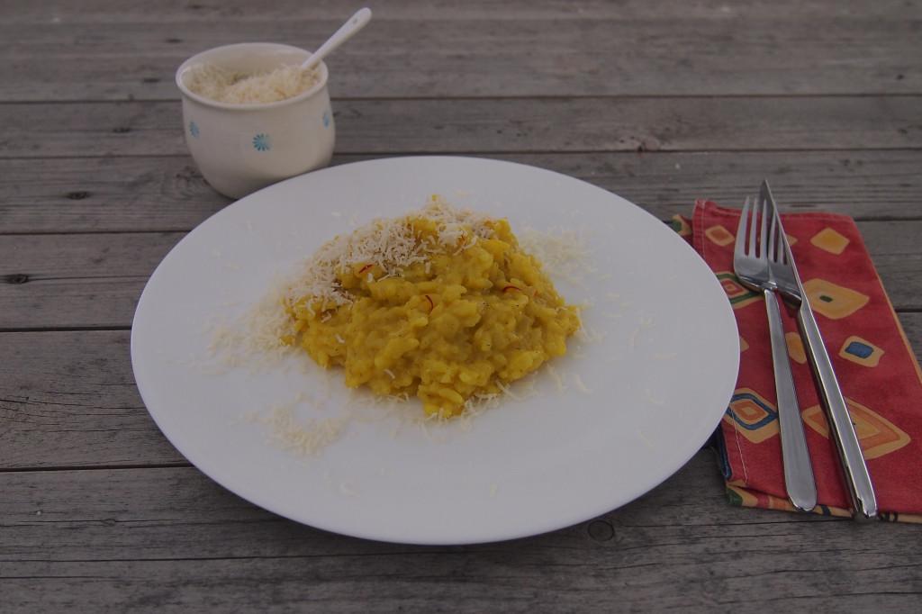 Nahaufnahme eines Tellers mit Risotto alla Milanese it Parmesan bestreut. Im Hintergrund Schälchen mit geriebenem Parmesan.
