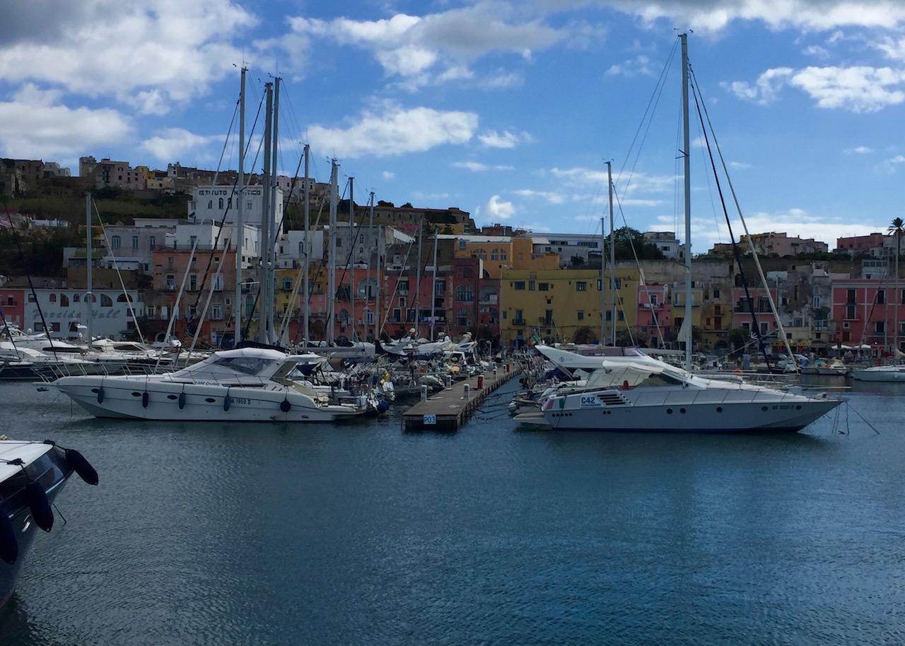 """Der """"kleine"""" Hafen von Procida mit Booten und den bunten Häuser"""